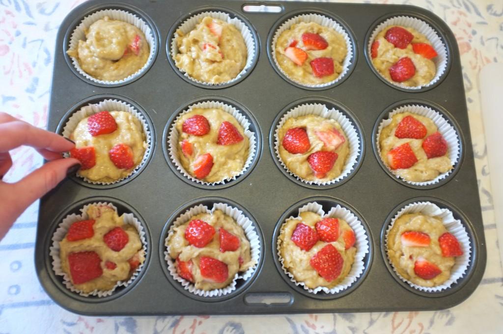 Les petits morceaux de fraises déposés sur le dessus de la pâte décorent les muffins