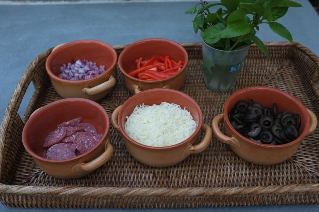 Les garnitures: oignons rouges, poivrons rouges, pepperoni, mozzarella, olives noires, basilique.
