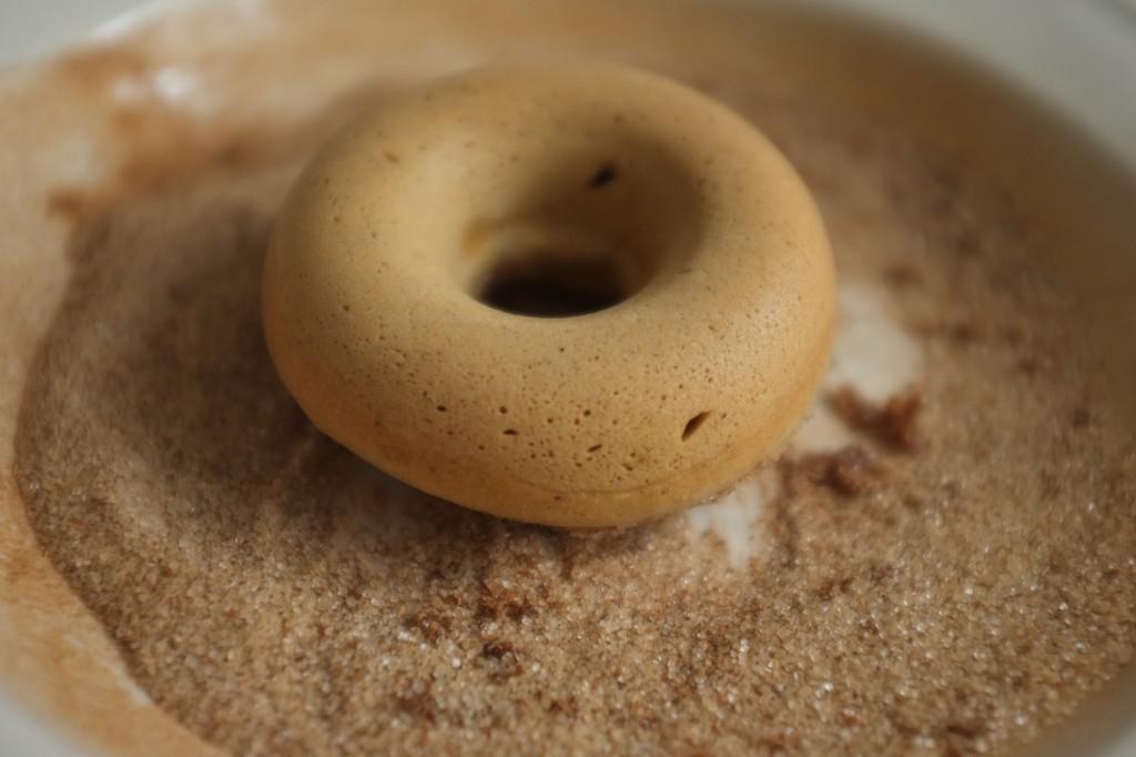 Le donut pré-trempé dans le beurre est ensuite posé dans le sucre à la cannelle