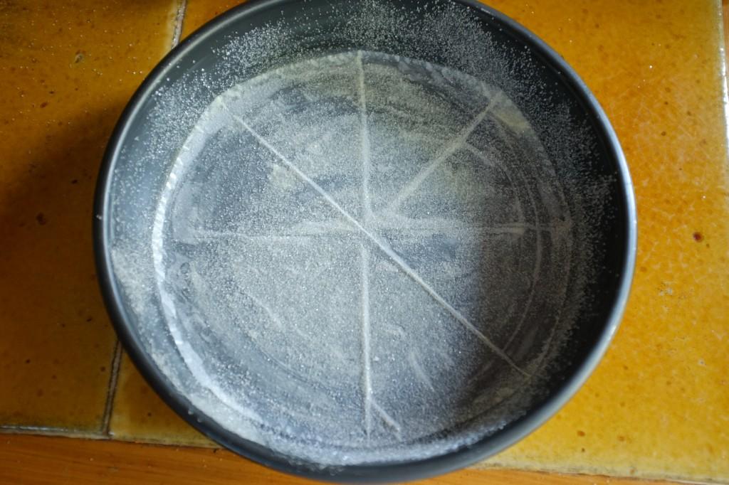 le moule beurré, le papier cuisson au fond et le tout saupoudré de sucre de canne