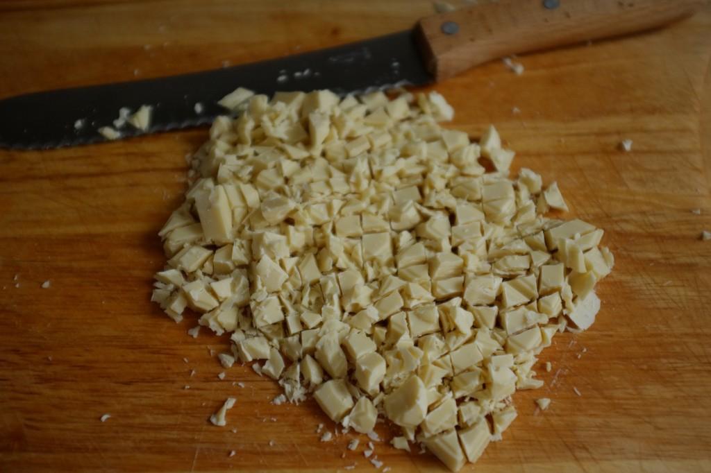 La plaque de chocolat blanc sans gluten est découpé en pépites à l'aide d'un couteau à pain