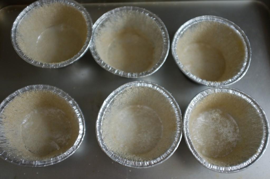Les petits moules individuels sont beurrés et saupoudrés de sucre de canne