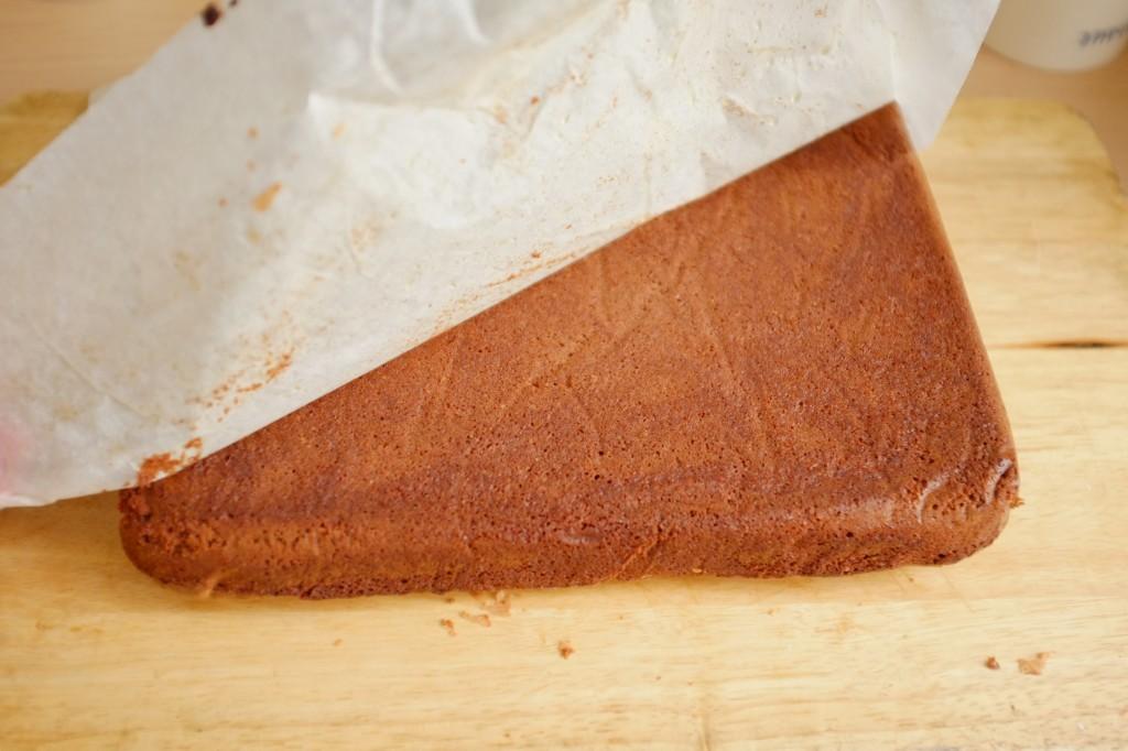 Le brownie chocolat est démoulé à l'envers sur une planche à découper, je pèle le papier cuisson.