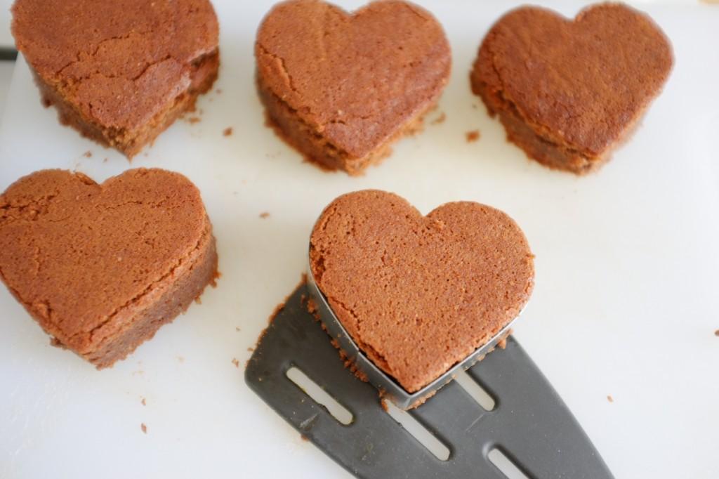 Les brownies sans gluten en forme de coeurs sont déposés sur une autre planche à découper.