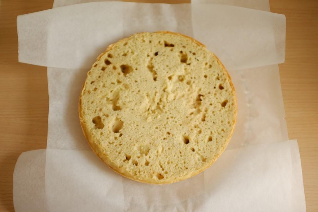Le premier gâteau est déposé sur la plat de service, lui-même protégé aux bords par des fines feuilles de papier cuisson