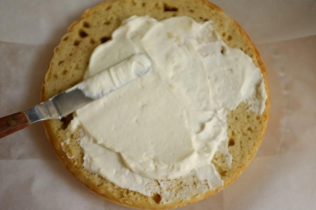 La crème au beurre coco est étalée sur le dessus du premier gâteau