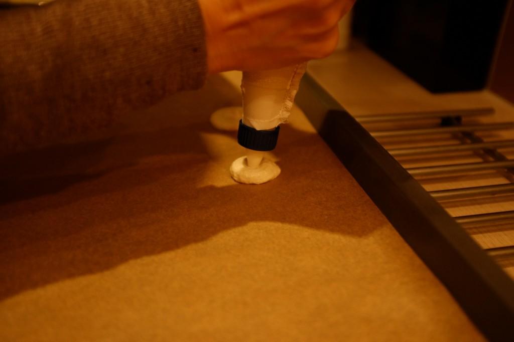 Une fois dans la poche à pâtisserie, la pâte est déposée sur la plaque de cuisson. La douille est tenue bien droite pour assurer un cercle de pâte bien rond