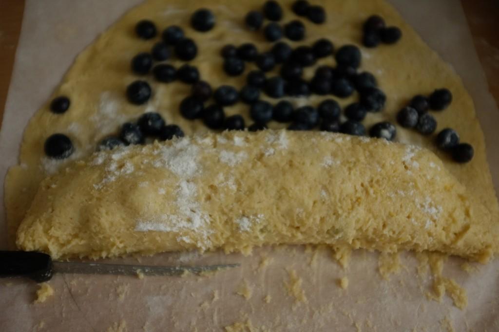 La pâte est alors roulée sur les myrtilles. Pour déolée plus facilement la pâte du papier cuisson, je farine régulièrement et je m'aide de la lame d'une couteau.