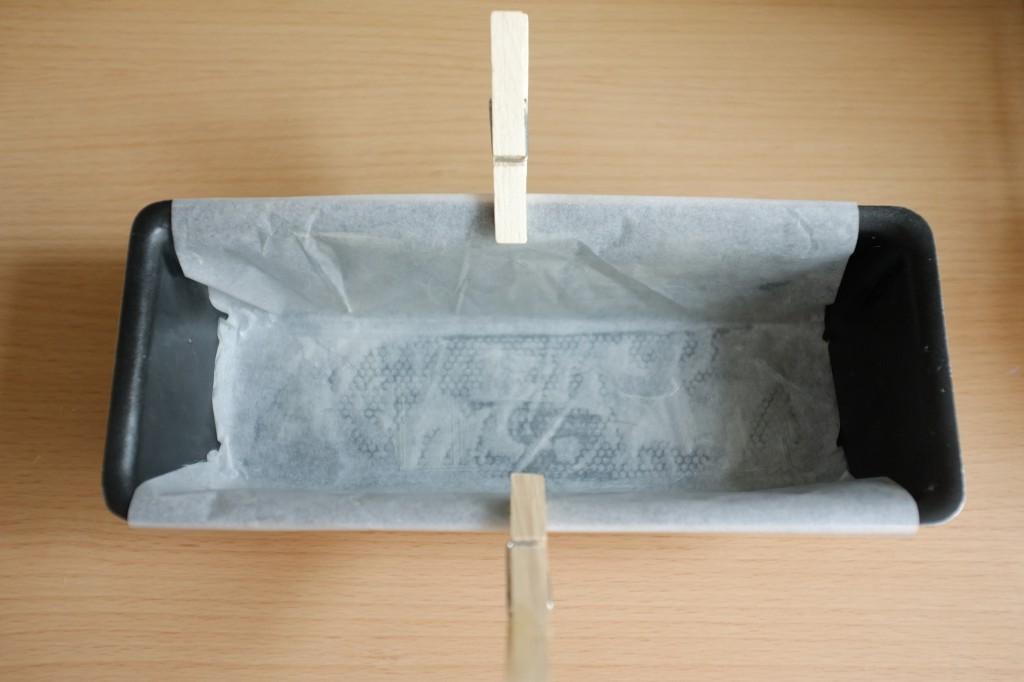 Le moule est beurré, puis recouvert d'un papier cuisson, puis beurré encore. Les bords dépasse pour aider à démouler le cake après cuisson.