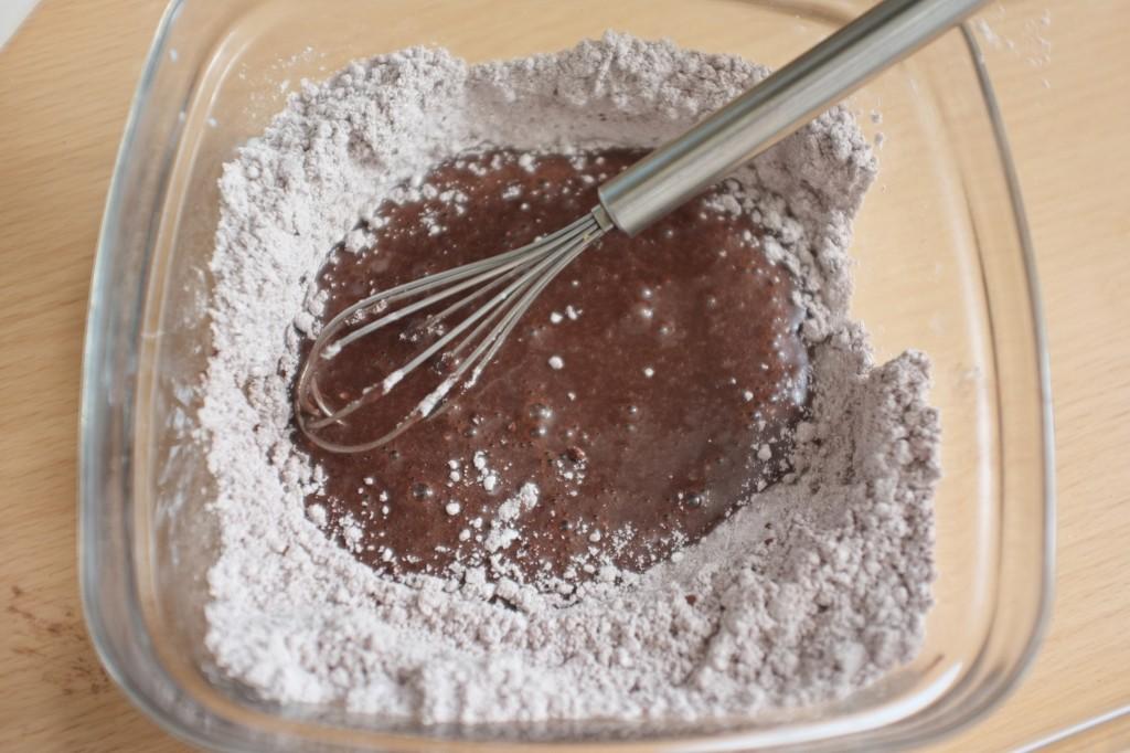Le sucre glace et le chocolat noir en poudre sans gluten sont mélangés ensemble pour le glaçage au chocolat