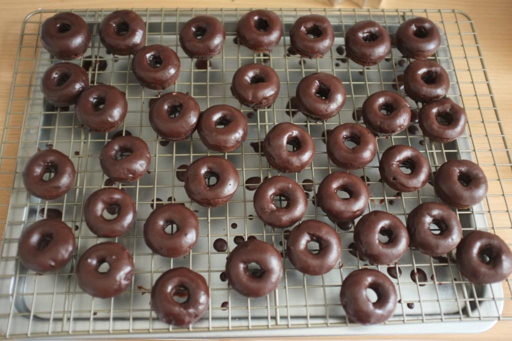 Les mini donuts sans gluten au chocolat, glaçés au chocolat sèchent sur une grille
