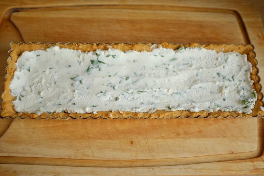 Le fond de tarte sans gluten est recouvert du mélange de fromage de chèvre frais et basilique