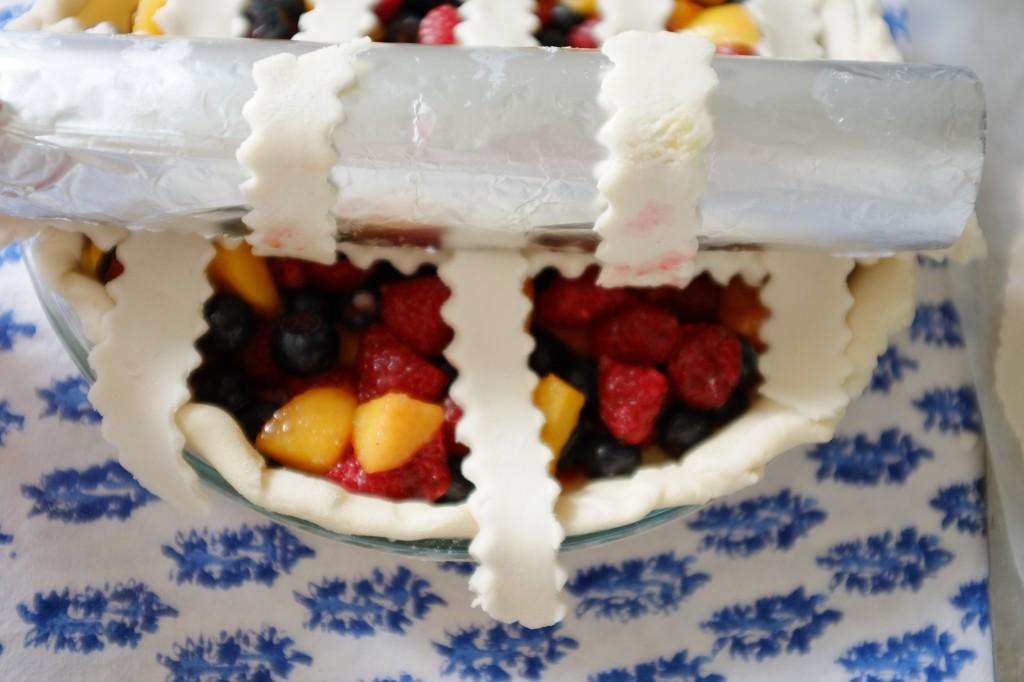 La dernière lamelle de pâte sans gluten est positionnée sur cette moitié de tarte.