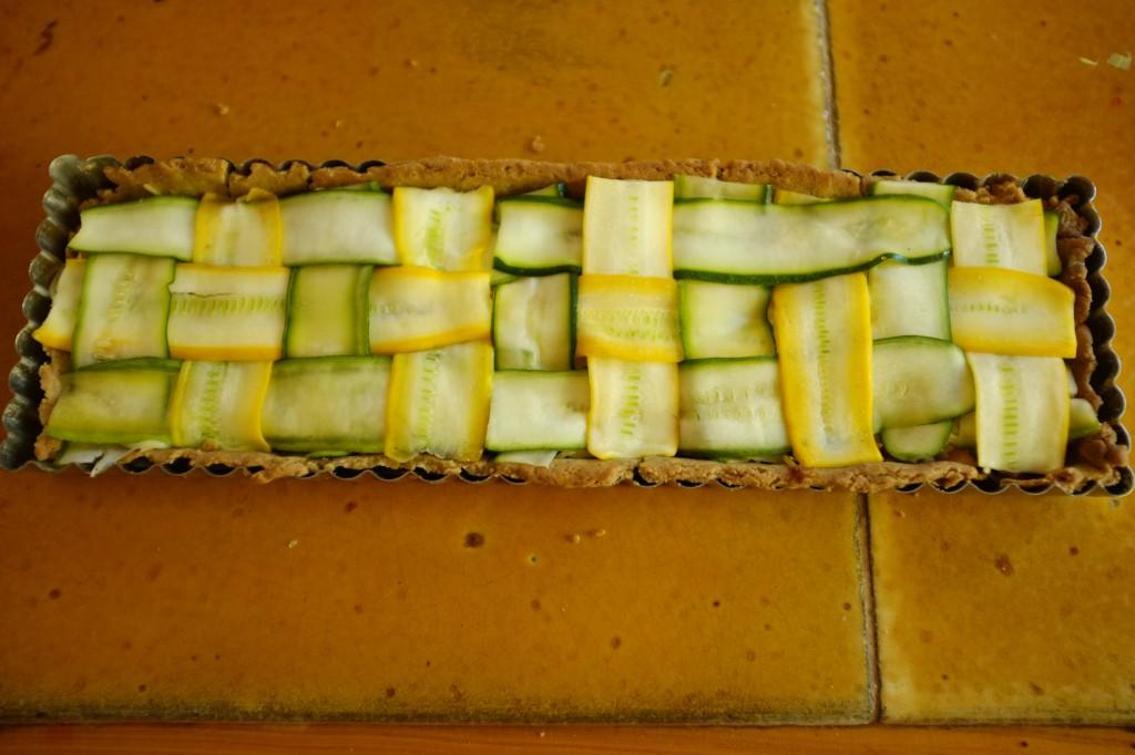 La tarte sans gluten courgette et poireau est tressée en alternace de courgettes jaunes et vertes