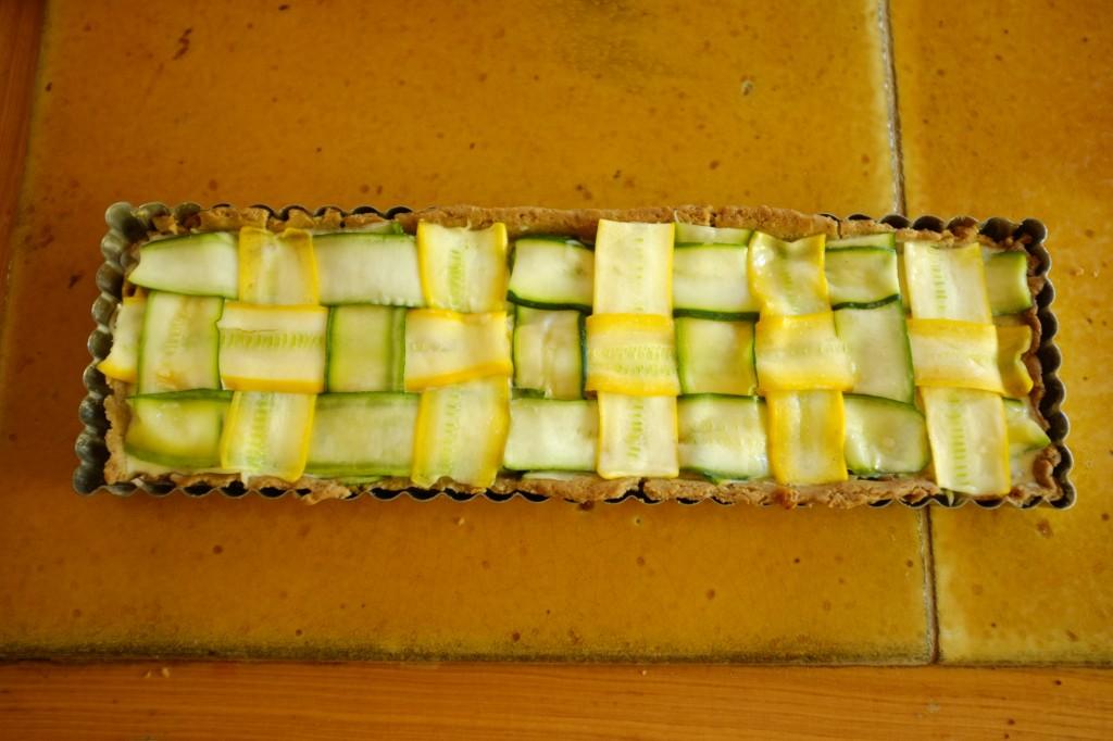Les lamelles de courgettes sont badigeonnées à l'huile d'olive, la tarte est prête à être enfournée