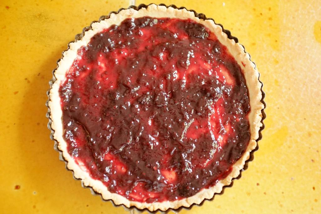 Le fond de tarte est recouvert de confiture de mûres