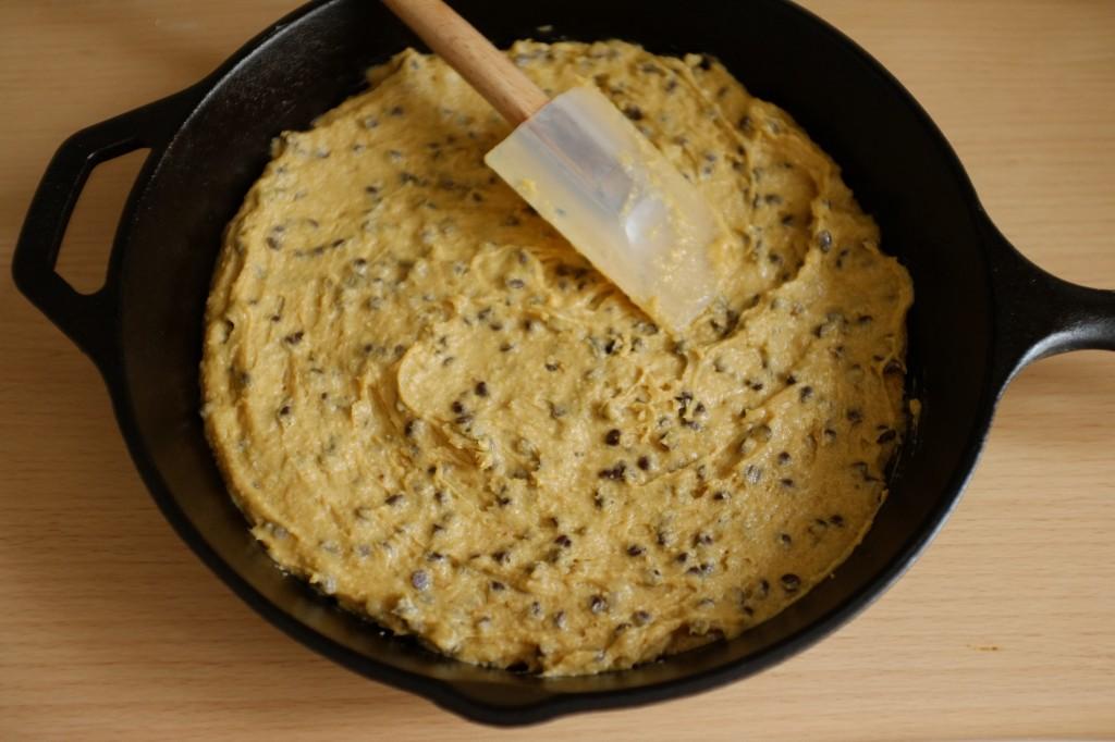 La pâte sans gluten de cookie au chocolat déposé dans une poêle en fonte avant d'être enfournée