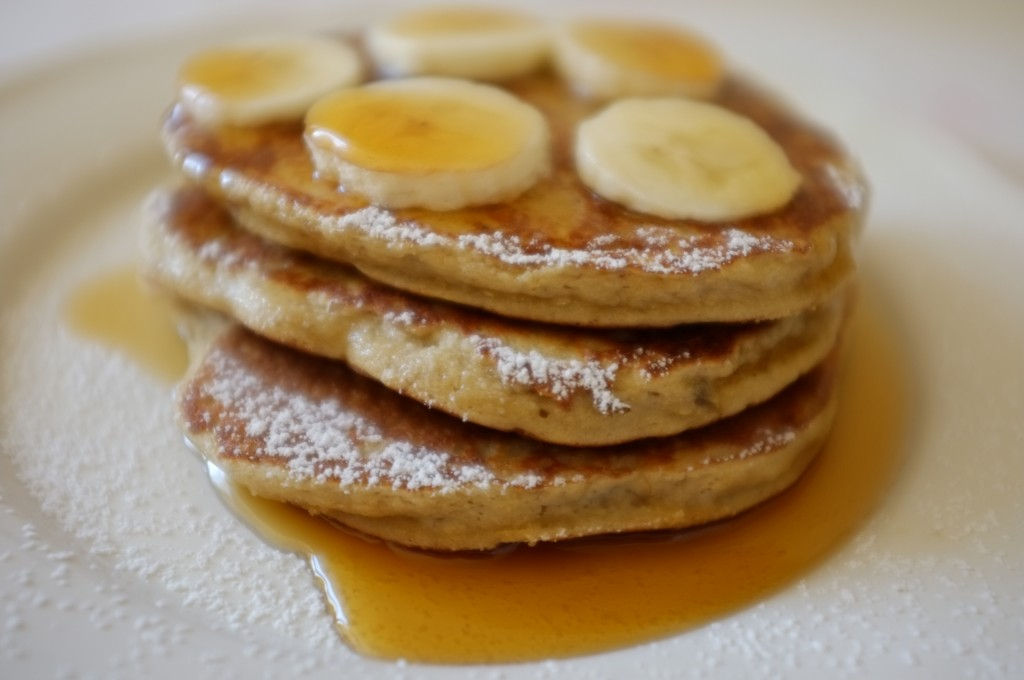 Les pancakes sans gluten noix de coco-banane, servies avec des rondelles de banane fraiches et du sirop d'érable