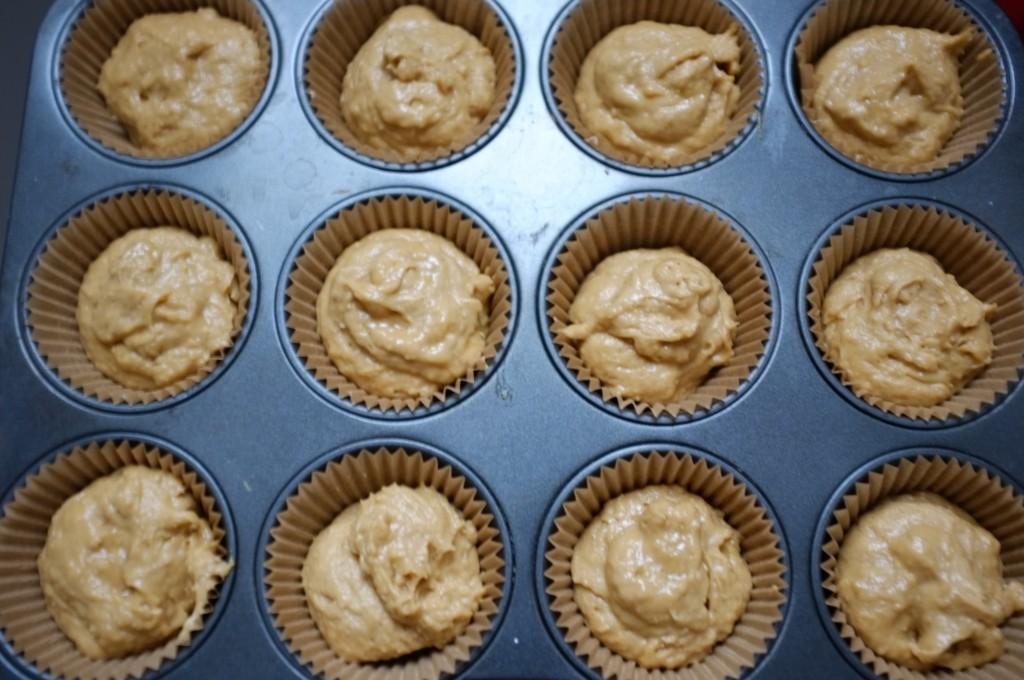 La pâte sans gluten est déposée dans les petits moules en papier de la plaque à muffin