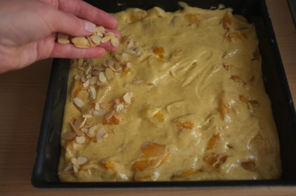 Une fois dans le moule, le gâteau est saupoudré d'amandes effilées légèrement parfumés à la cannelle.