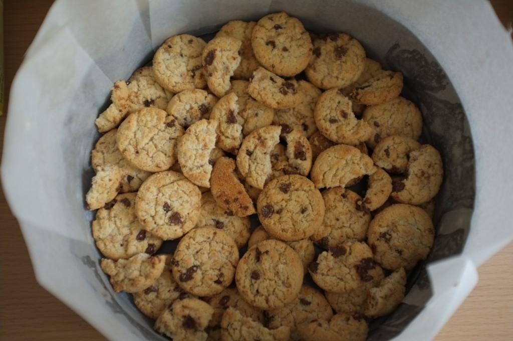 Les cookies sans gluten sont déposés au fond du moule formé un fond de gâteau bien épais. On apperçoit les hauts bords du papier cuisson.