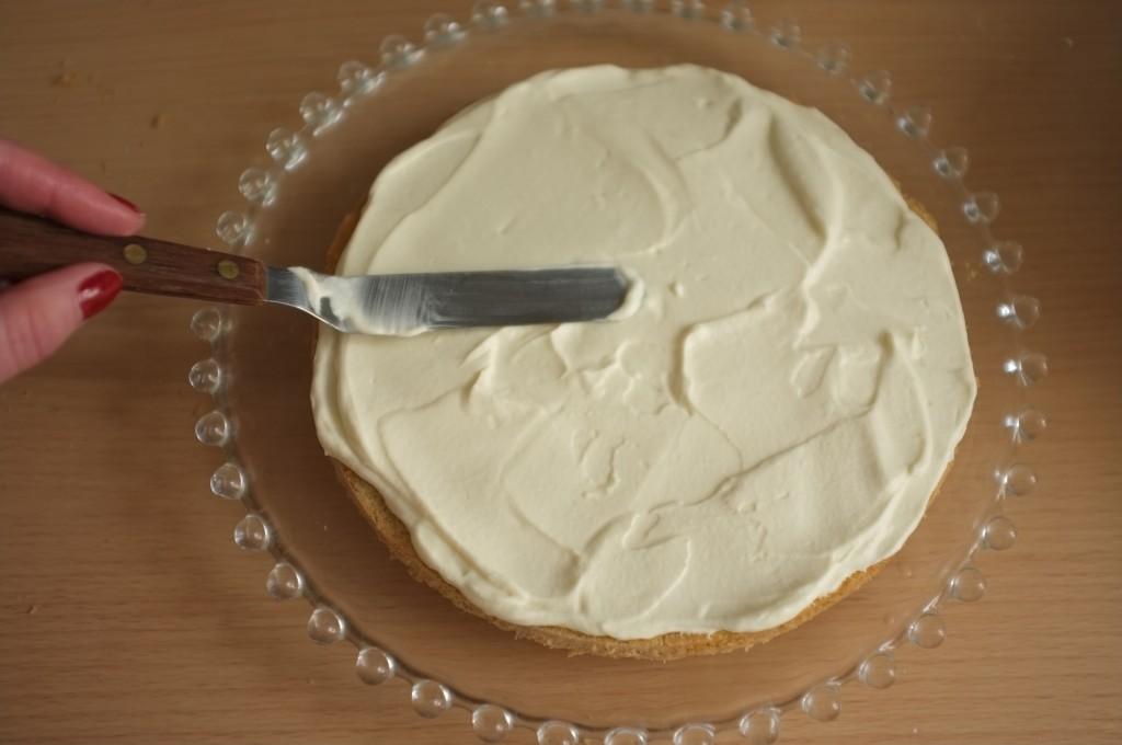La crème chantilly maison est généreusement étalée sur le premier gâteau sans gluten