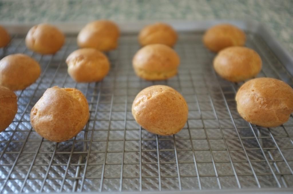 Les petits choux sans gluten refroidissent tranquillement sur une grille.