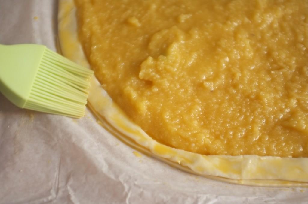 Le bords, puis ensuite le rebord avec un peu de pâte, sont badigeonnés de glaçage à l'oeuf pour bien se coller.