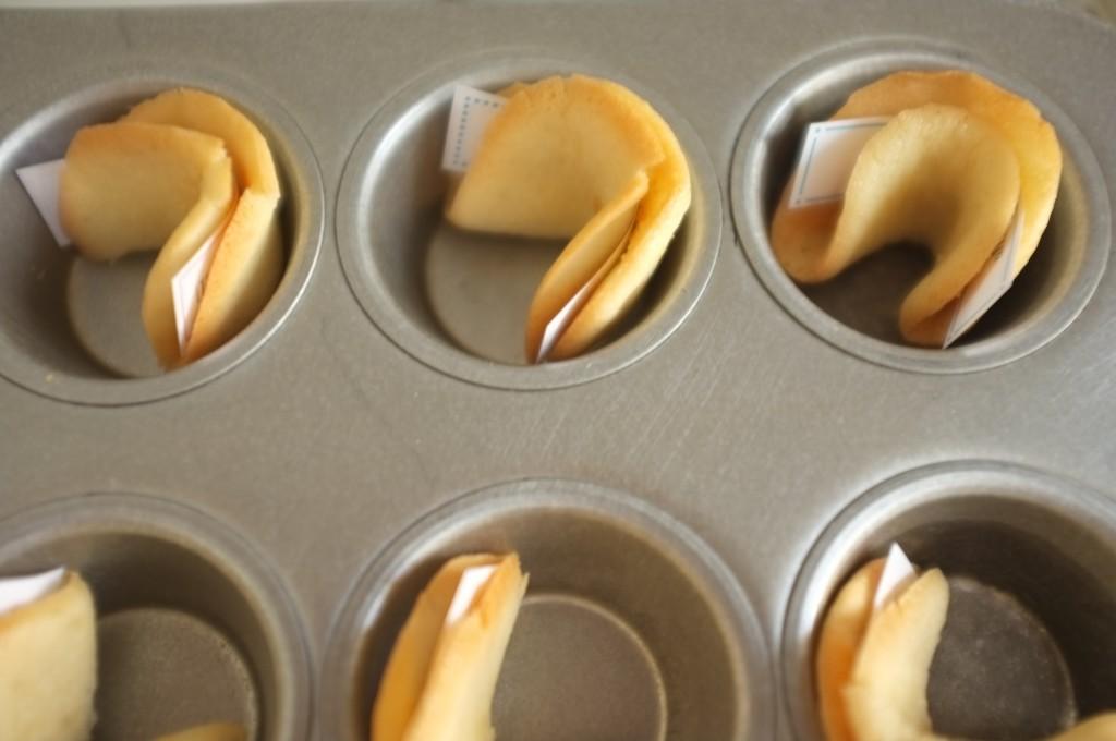 """les """"fortune cookie"""" chinois sans gluten refroidissent plié dans les cavité d'une plaque à mini muffins."""