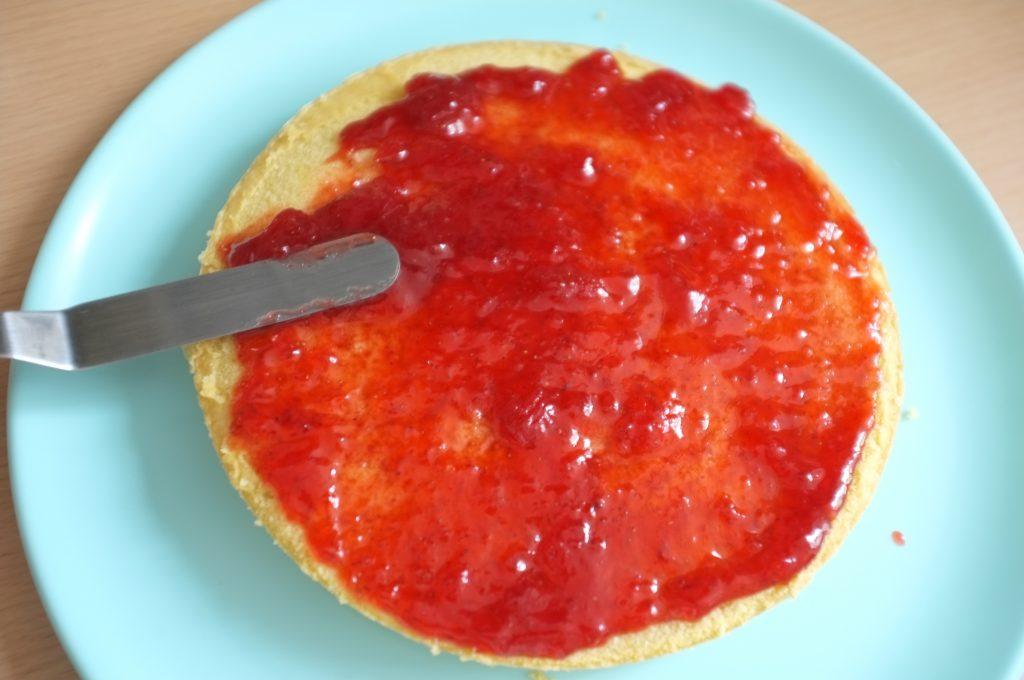 La première génoise sans gluten est recouverte de confiture de fraise.