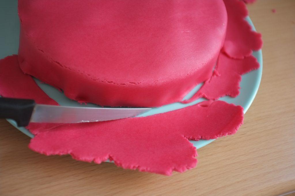 Je découpe délicatement la pâe à sucre sur les bords du gâteau.