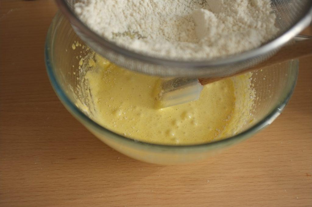 Je tamise les ingrédients secs au dessus des jaunes d'oeufs blanchi pour éviter les petits grumeaux de la poudre d'amande.