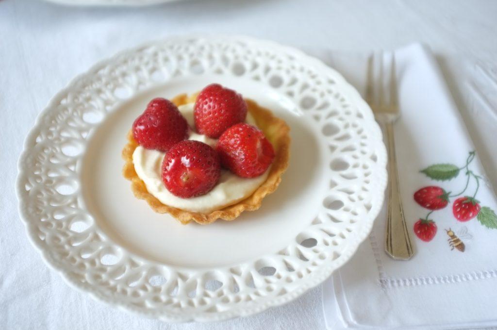 La tartellette sans gluten aux fraises, avec 4 belles fraises, déposé sur de la crême fouettée